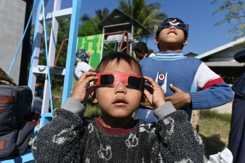 """Children use eclipse glasses to watch a rare """"ring of fire"""" solar eclipse in Wan Twin in central Myanmar, on Dec 26, 2019."""