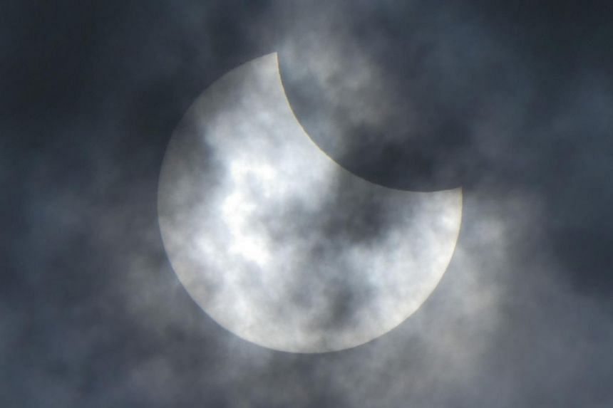 """The Moon moves in front of the Sun during the start of a rare """"ring of fire"""" solar eclipse in Jakarta, on Dec 26, 2019."""