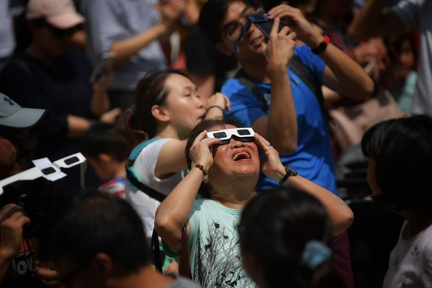 People view the annular solar eclipse at the Kebun Baru Spring Amphitheatre in Ang Mo Kio, on Dec 26, 2019.