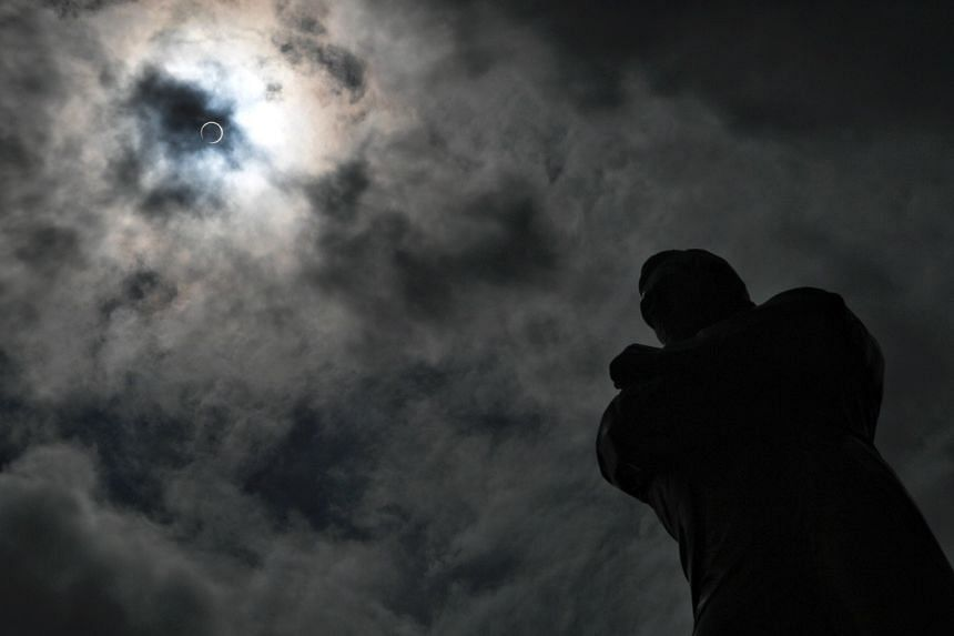 The silhouette of the Stamford Raffles Statue is seen during the eclipse at around 1.24pm at the Arts House, on Dec 26, 2019.