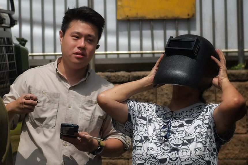 Mr Poon Jun Long (left) lending his welding mask to a passer-by to view the annular solar eclipse in Ang Mo Kio on Dec 26, 2019.