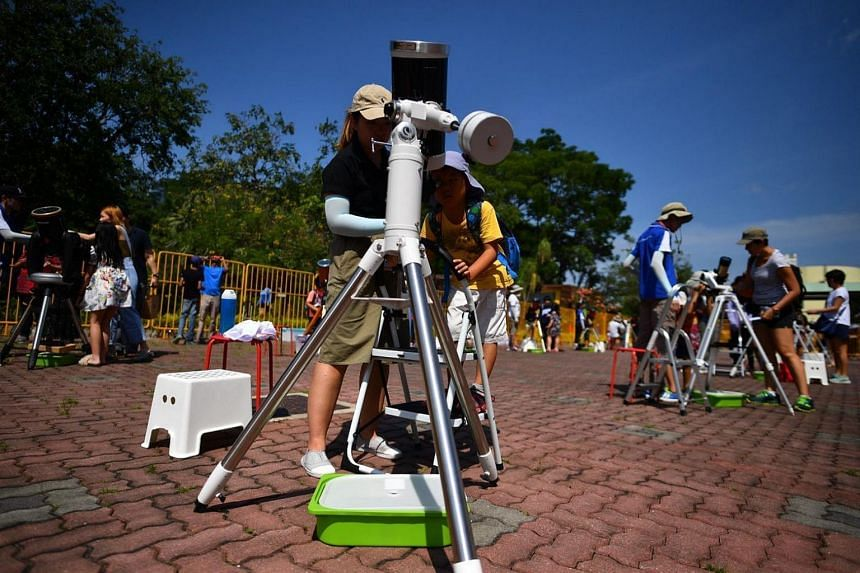Six-year-old Gideon Chew (right) viewing the solar eclipse through a telescope with Science Educator Lim Huan at the Science Centre Singapore.