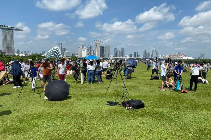 People looking at the annular solar eclipse at the Marina Barrage at 12pm, on Dec 26, 2019.