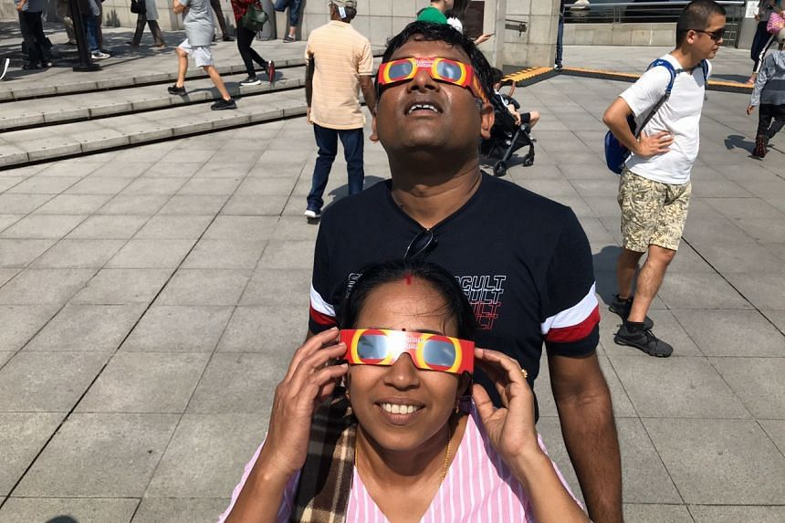 Tourists at Merlion Park looking at the annular solar eclipse, on Dec 26, 2019.