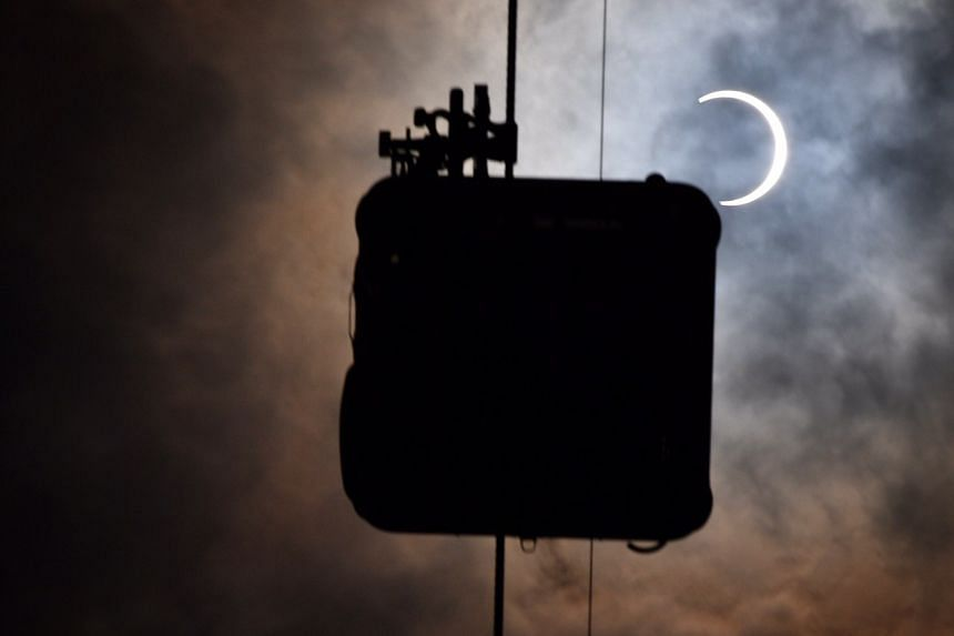 The annular solar eclipse juxtaposed against a cable car at Harbourfront Tower on Dec 26, 2019.