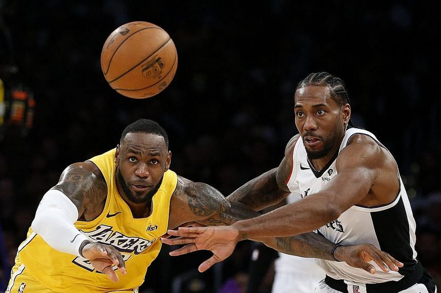 The Los Angeles Lakers' LeBron James vying for a loose ball with the Clippers' Kawhi Leonard during the second half of their NBA game on Wednesday. The Clippers forward's game-high 35 points, including 11 in the final quarter, helped his team overtur
