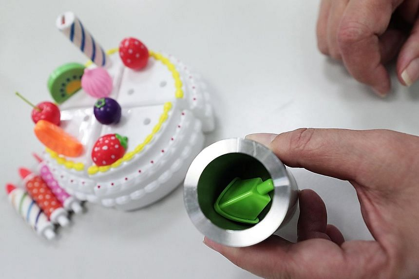 Clockwise from far left: A small-parts tester that simulates the windpipe of a three-year-old to test if a toy is a choking hazard. Ms Tham Yoke Chun showing that a baby cot should have a minimum 30cm drop-side in an open position, to prevent a baby