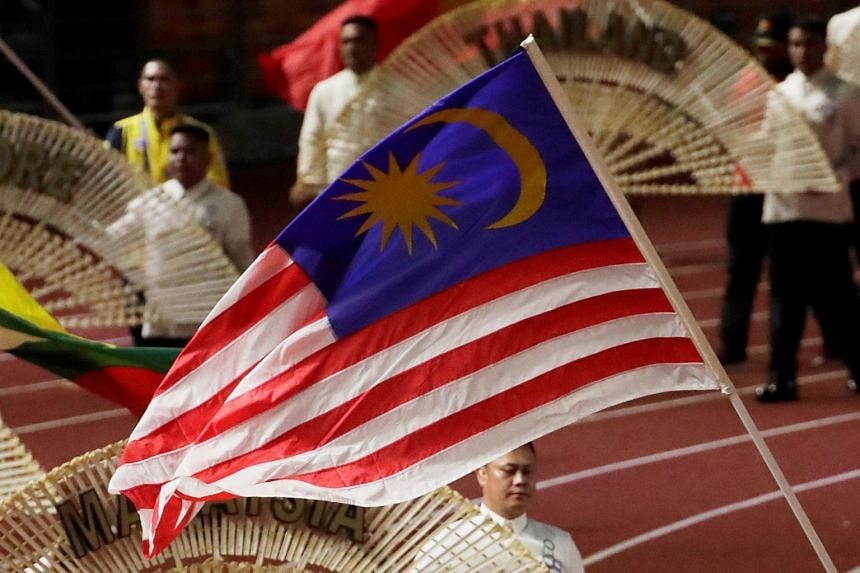 The Malaysian flag seen at a sports event. Khat, as Jawi calligraphy is called in Malaysia, is the writing of the Malay language using Arabic script.