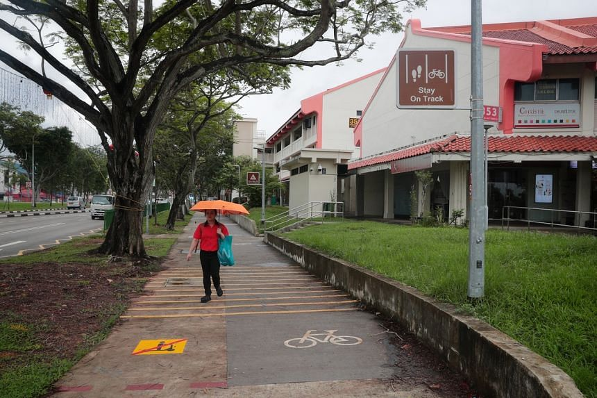 A pedestrian walking along a footpath in between the road and a cycling path, along Jurong East Street 31, on Dec 17, 2019.