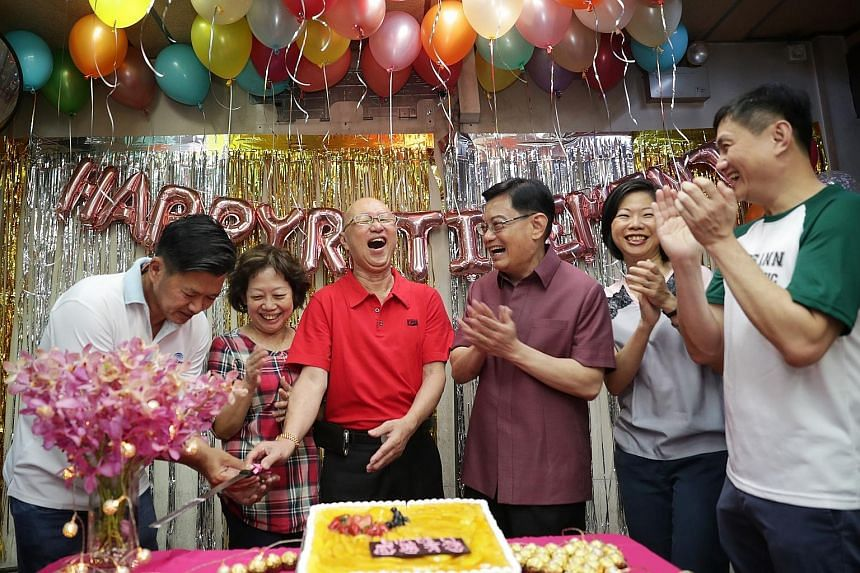 Mr Lim Kok Peng (in red) with his wife Chen Meng Keun beside him at a farewell party organised by residents yesterday. The couple are retiring after running Lim De Li minimart in Toh Yi for almost 20 years. With them at the party were (from left) grassroo