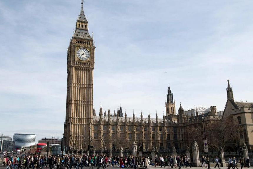 In a photo taken on March 30, 2017, people walk in front of the Houses of Parliament and Elizabeth Tower in London.