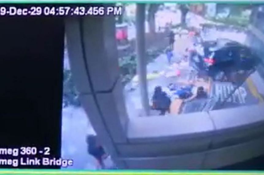 The car accelerates onto the pavement, hitting some Filipinos having a picnic, before crashing into the railing and plunging to the car park exit road below.