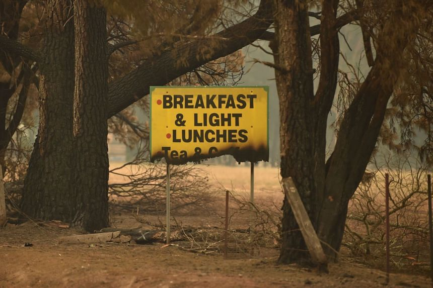 A sign is seen half burnt after bush fires ravaged the town of Bilpin, 70km west of Sydney, on Dec 29, 2019.