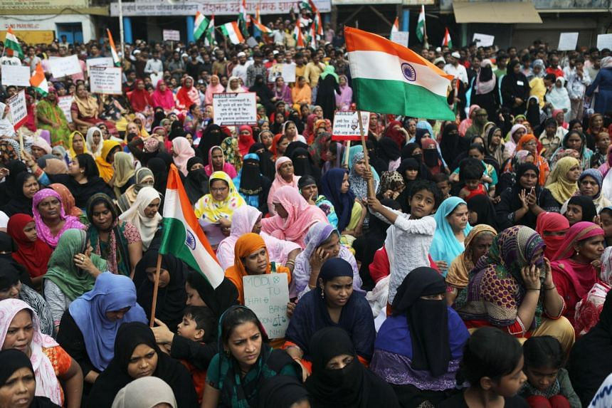 Demonstrators hold placards and wave an Indian national flag during a protest against a new citizenship law in Mumbai, on Dec 29, 2019.