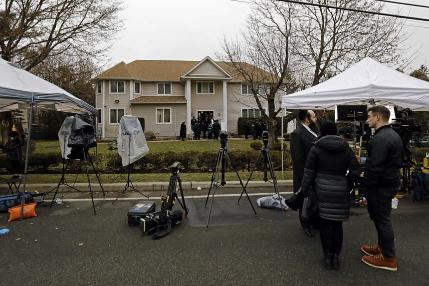 Members of the media staked out in front of the home of Hasidic rabbi Chaim Leibush Rottenberg where the attack took place, on Dec 29, 2019.