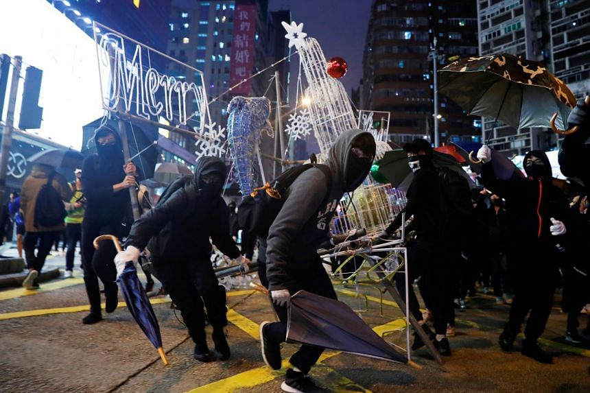 Anti-government protesters tear down Christmas and New Year's decorations during a demonstration on New Year's Eve outside Mong Kok police station in Hong Kong.