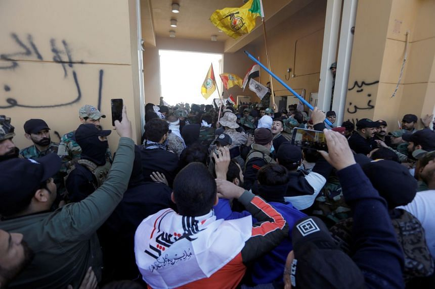 Protesters and militia fighters enter the the US Embassy.