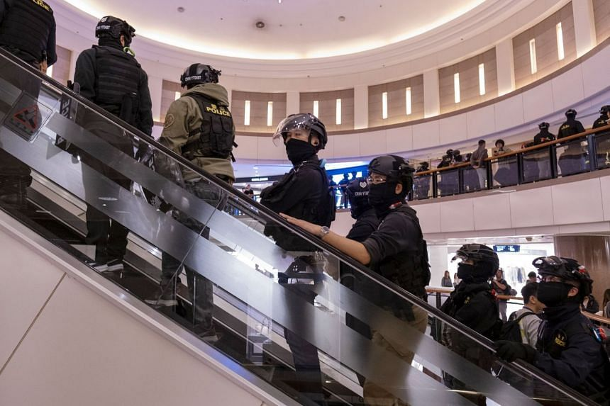 Riot police ride an escalator as they patrol the Harbour City shopping mall in the Tsim Sha Tsui district.