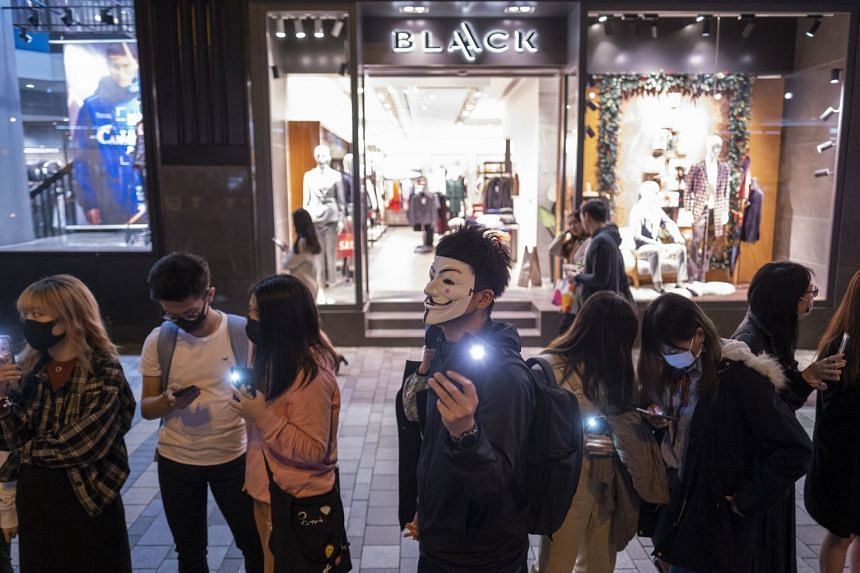 Demonstrators shine lights from their smartphones as they form a human chain during a protest on Nathan Road in the Tsim Sha Tsui district of Hong Kong.