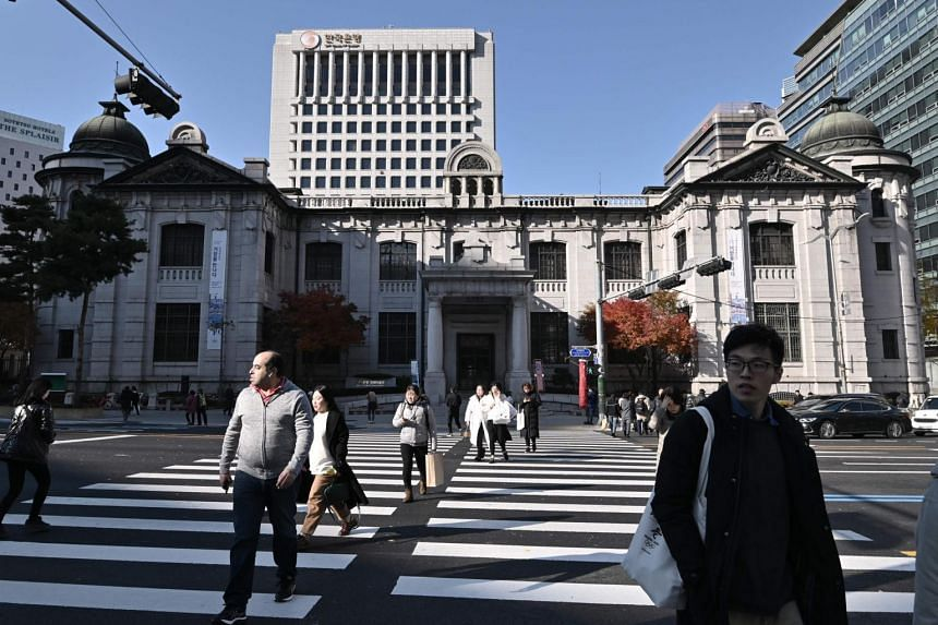 Pedestrians use a crosswalk in front of the Bank of Korea in Seoul on Nov 29, 2019. The average rate of inflation for all of 2019 came to a record-low 0.4 per cent.
