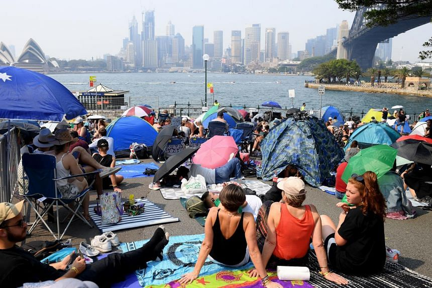 People claim early harbourside positions in Kirribilli ahead of the New Year's Eve fireworks display in Sydney on Dec 31, 2019.