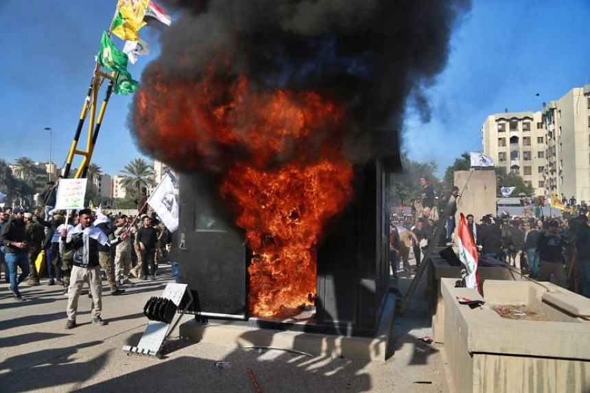 Protesters burn property in front of the US embassy compound, in Baghdad, Iraq, on Tuesday, Dec. 31, 2019. Dozens of angry Iraqi Shiite militia supporters broke into the US Embassy compound in Baghdad after smashing a main door and setting fire to a