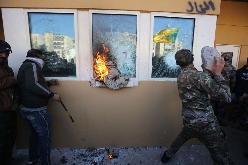 Members the Hashed al-Shaabi, a mostly Shi'ite network of local armed groups trained and armed by powerful neighbour Iran, smash the bullet-proof glass of the US embassy's windows.