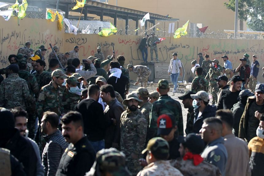 Iraqi protesters breach the outer wall of the diplomatic mission.