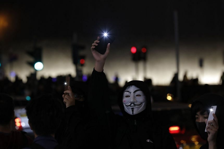 People raise their mobile phone lights as they form a human chain on New Year's eve in Hong Kong.