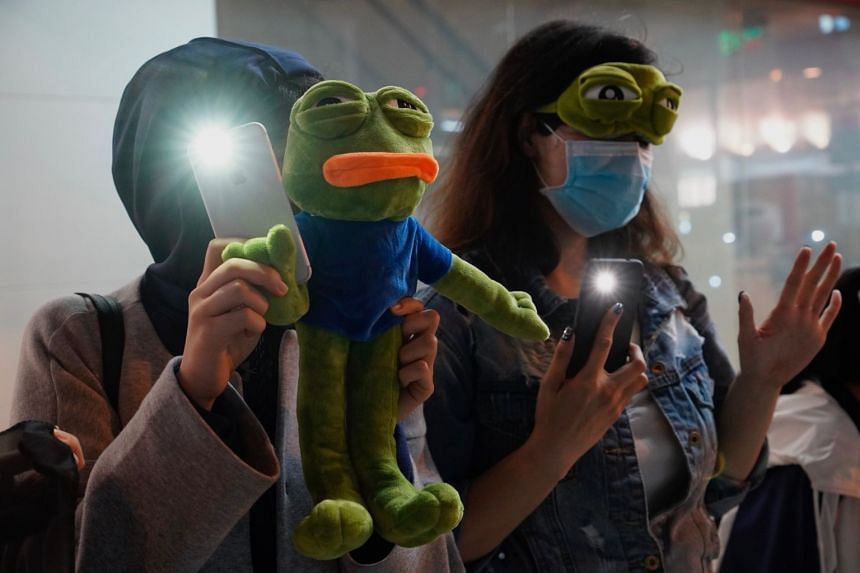 People raise their cellphones lights and stuffed frog toy as they form a human chain on New Year's eve in Hong Kong.