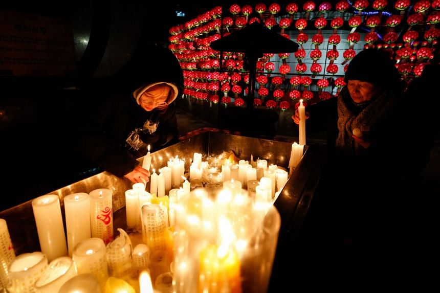 South Korean Buddhist devotees light candles as they pray at the Jogyesa temple on New Year's Eve in Seoul.