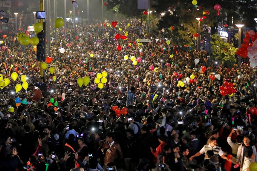 People light up their mobile phones as they celebrate the New Year's countdown event in a road in Ahmedabad, India.