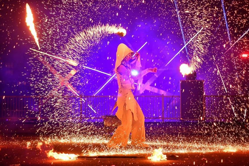 A fire twirler performs during the countdown.