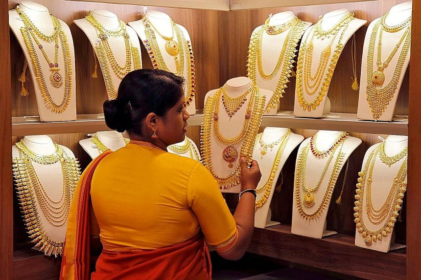 A saleswoman picking gold necklaces to show to a customer at a jewellery showroom in Kochi, India, in May. Spot gold rose 0.3 per cent to US$1,514.97 an ounce as of 1.51pm in New York on Monday, extending its December gain to 3.5 per cent, according