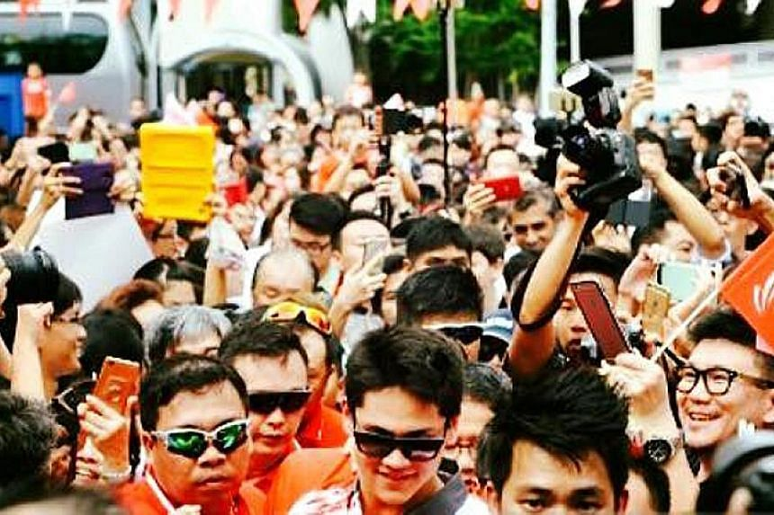 Left: Mr Edwin Cheong (front, in green sunglasses) providing protection services to swimmer Joseph Schooling during a victory parade in 2016 after the latter's Olympic win. PHOTO: FRANCIS CHNG Above: Ms Wendy Hon was part of the team protecting rock