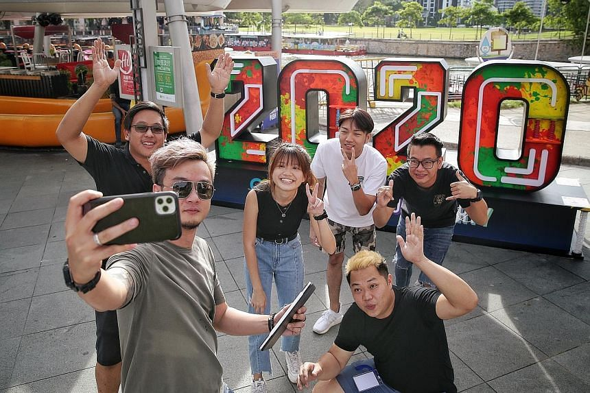 """An events crew taking photos yesterday in front of their company's handiwork, a neon """"2020"""" photo wall display at Clarke Quay, ahead of New Year's Eve celebrations last night. Prime Minister Lee Hsien Loong said in his New Year message that having be"""