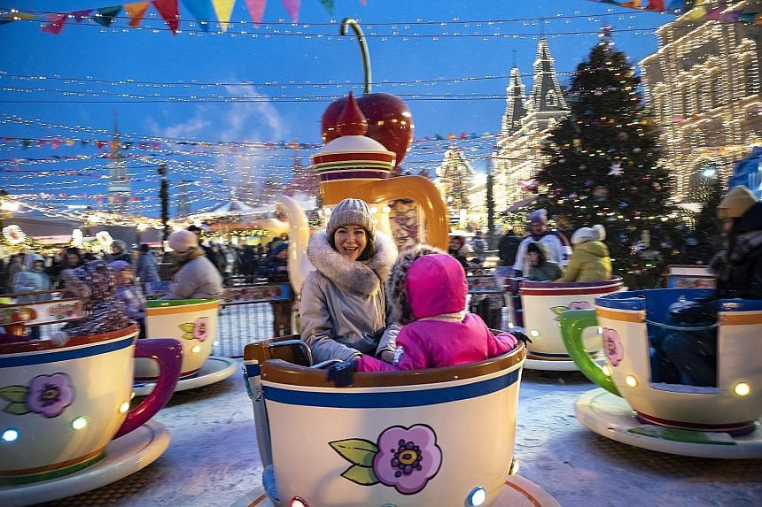 Muscovites in holiday mood at Red Square, which has been decorated for Russia's New Year and Orthodox Christmas celebrations. PHOTO: ASSOCIATED PRESS