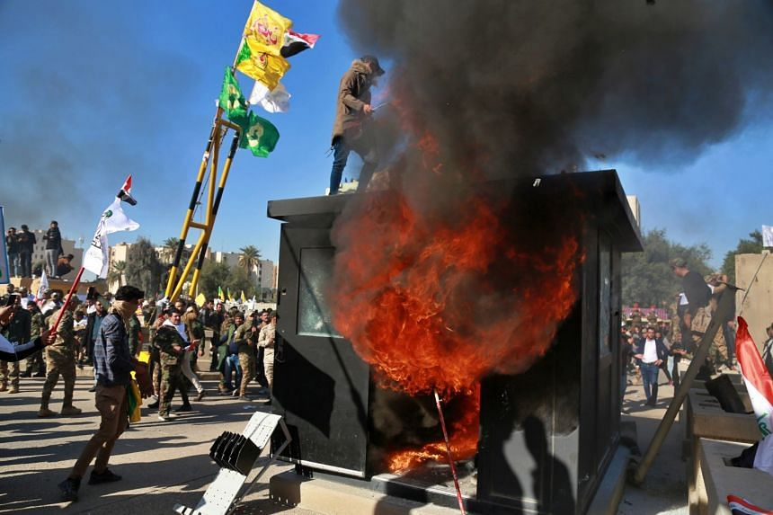 Protesters burn property in front of the US embassy compound, in Baghdad, Iraq.