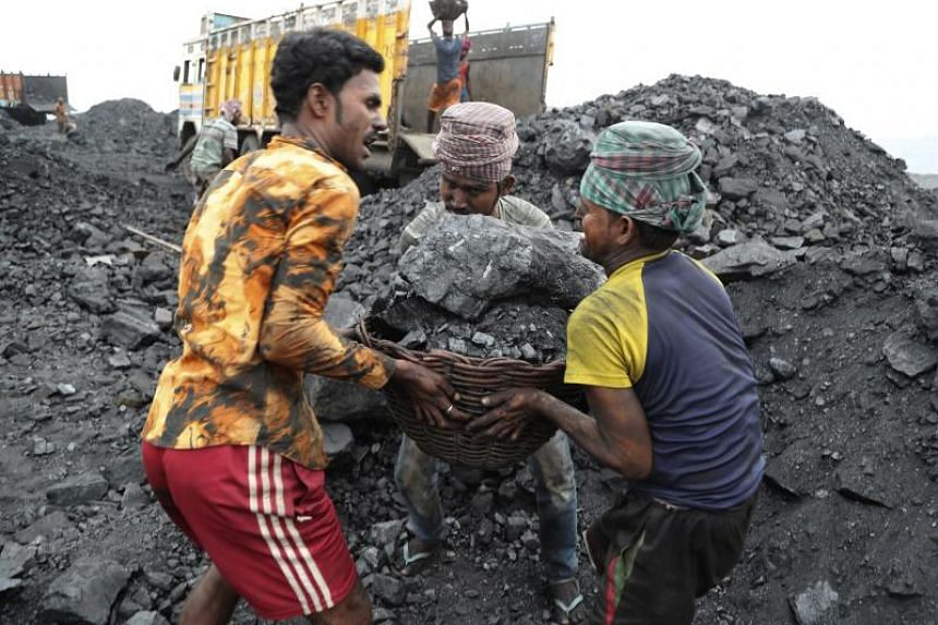 In a photo taken on Oct 23, 2019, labourers lift a large basket filled with coal before loading it into a truck for transportation in the village of Godhar in Jharia, India.
