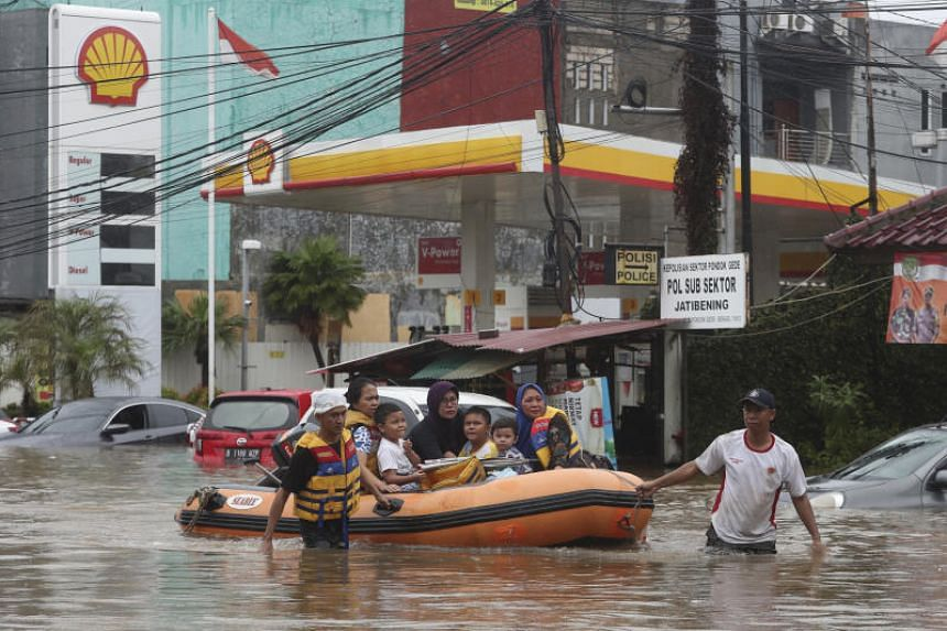 Indonesia rescue team evacuate residents from their flooded house at Jatibening on the outskirt of Jakarta, on Jan 1, 2020.
