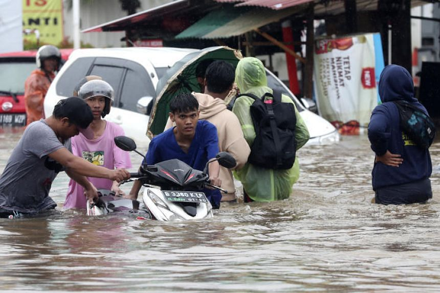 Indonesian people wade through floodwaters at Jatibening on the outskirt of Jakarta, on Jan 1, 2020.