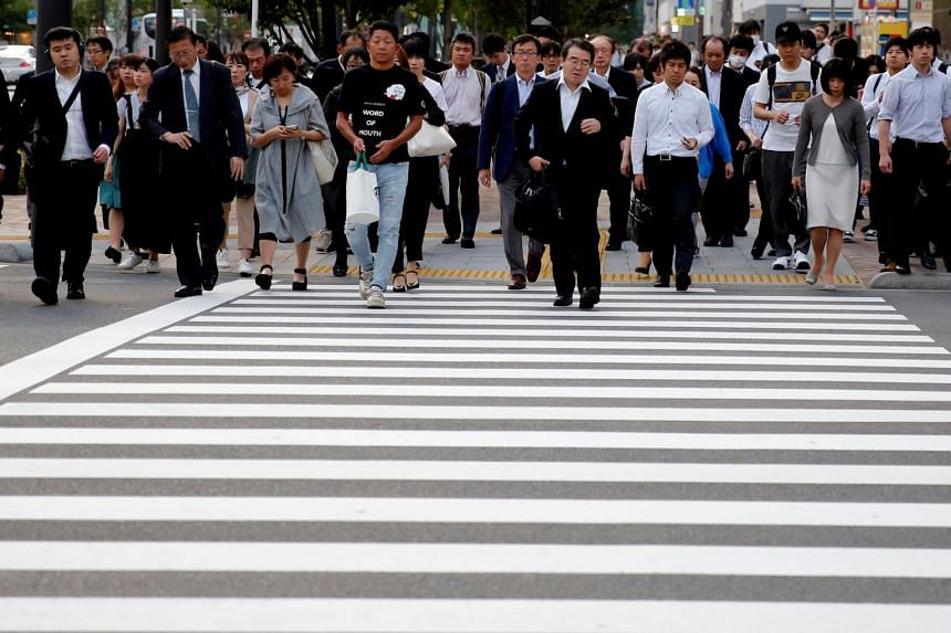 Pedestrians make their way in a business district in Japan on May 16, 2018. The raft of measures planned includes vocational training and grants for local governments that hire these people.