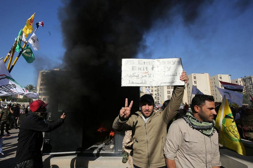 An Iraqi protester holds up a sign that was detached from the US embassy wall as a sentry box is set ablaze.