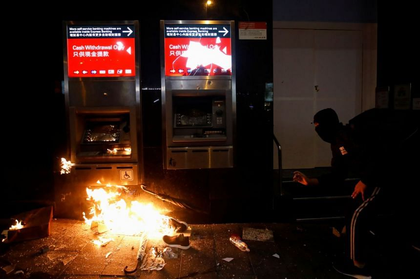 A protester vandalises an ATM during in Hong Kong on Jan 1, 2020.