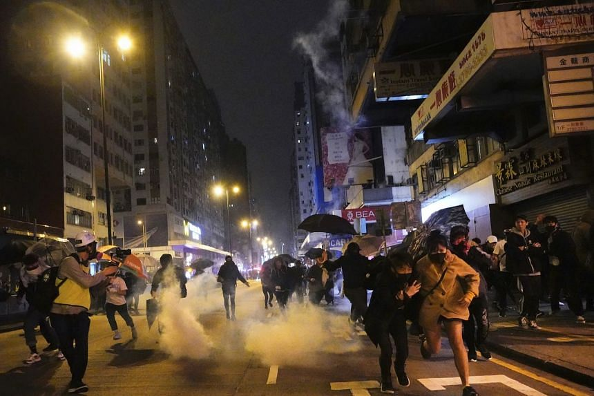 Protesters react as police fire tear gas during a demonstration in Hong Kong, early on Jan 1, 2020.