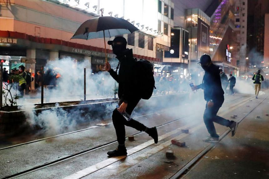 Protesters run as tear gas is fired in Hong Kong on Jan 1, 2010.