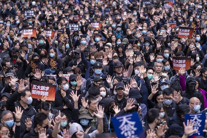 Protesters in Hong Kong's Hennessy Road yesterday. Demonstrators rang in the new year with a mass march through downtown areas.