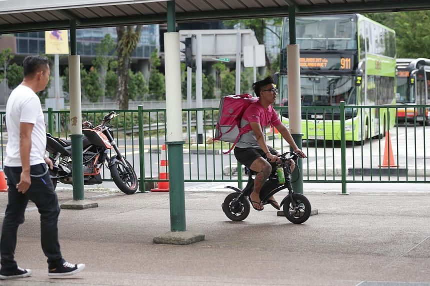 Land Transport Authority officers outside Compass One mall in Sengkang yesterday. Besides taking action against errant e-scooter users, they also checked devices such as power-assisted bicycles (above) to ensure they complied with the authorities' sa
