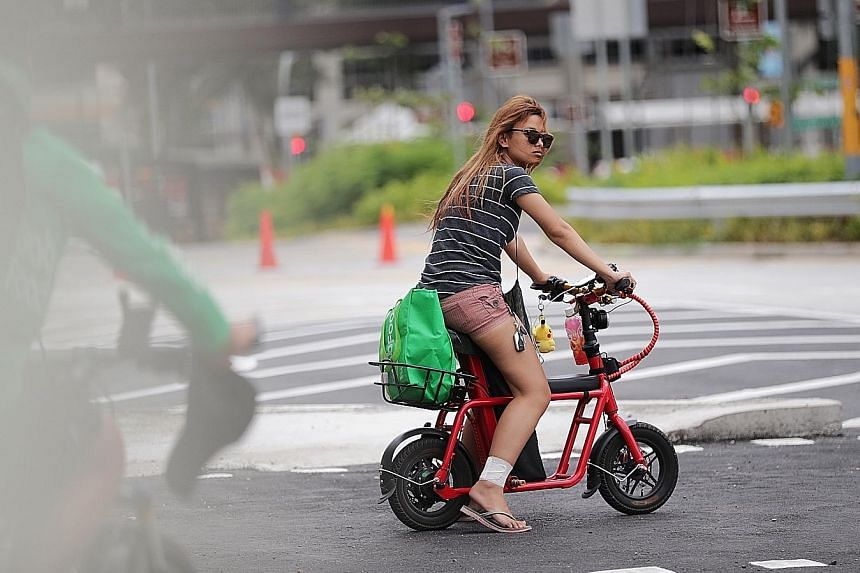 Electric scooter riders outside Causeway Point in Woodlands yesterday. When The Straits Times visited the mall in the afternoon, seven e-scooter users on footpaths were sighted within 30 minutes.