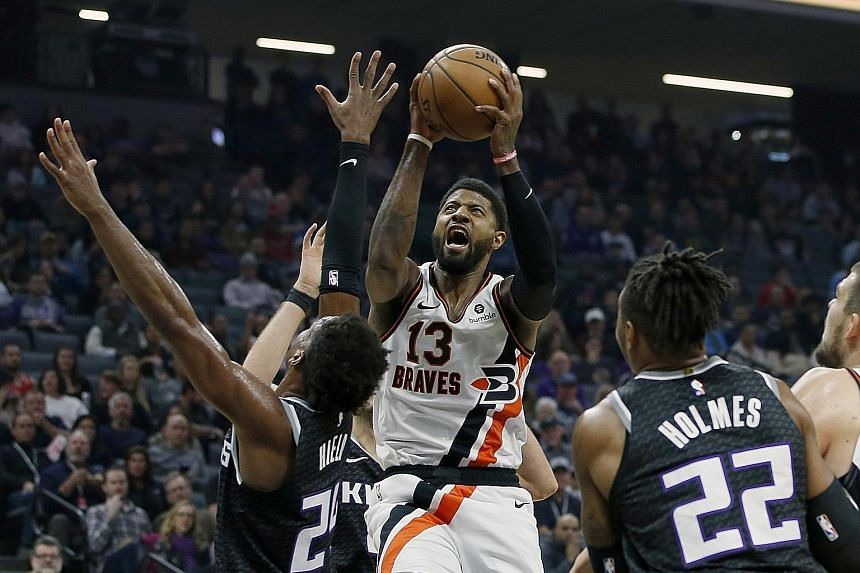 Los Angeles Clippers forward Paul George (centre) going to the basket between Sacramento Kings' Buddy Hield and Richaun Holmes in their NBA game on New Year's Eve. He shook off a slow start to score 21 points with season highs of 11 rebounds and nine